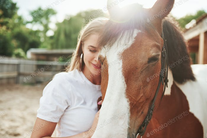 Peace and quiet. Happy woman with her horse on the ranch at daytime