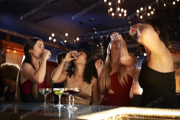 Group Of Female Friends Drinking Shots In Cocktail Bar Together