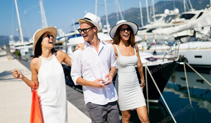 Vacation, travel, sea, friendship and people concept. Smiling friends having fun together