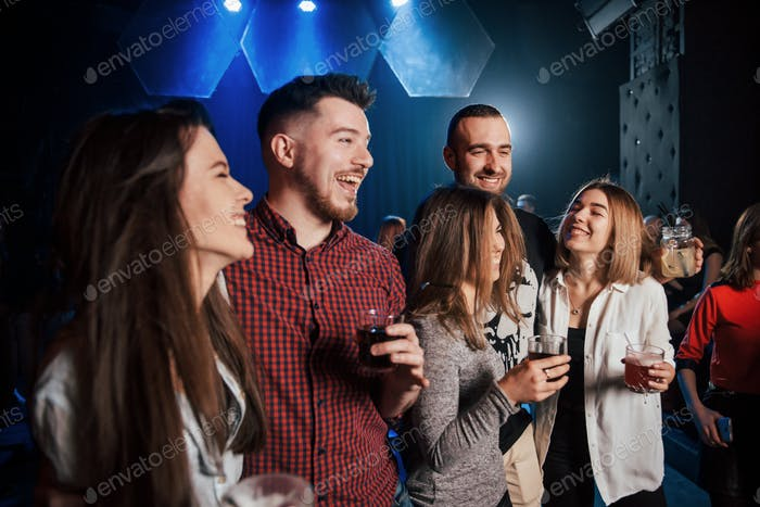 Making a jokes. Beautiful youth have party together with alcohol in the nightclub