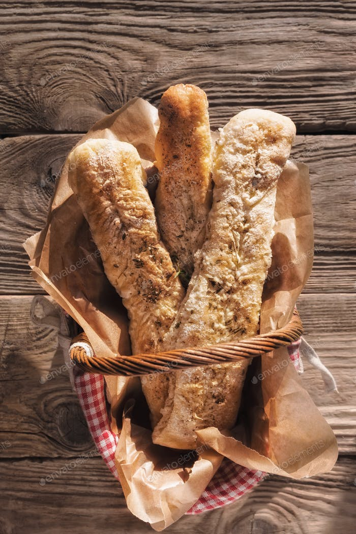 Homemade baguettes in the basket on the old boards