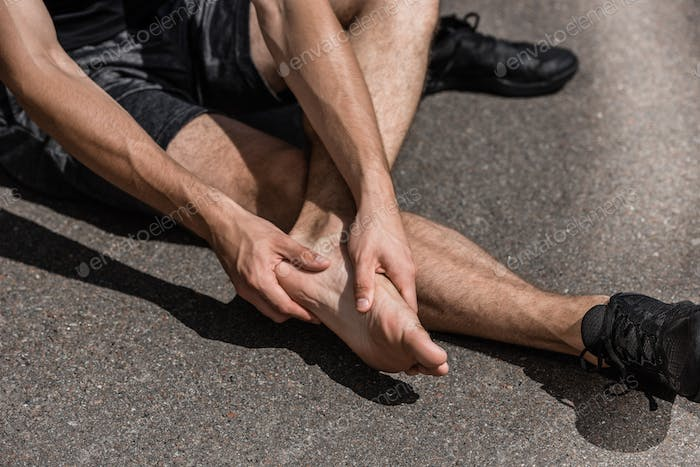 partial view of barefoot sportsman with foot pain on street