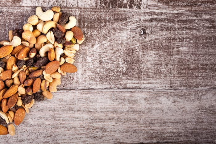 Half of heart shape Mix of healthy raw nuts on wooden background