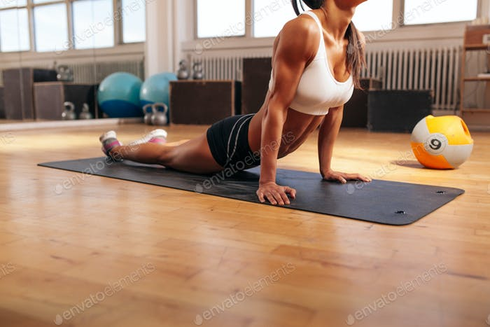 Muscular female doing stretching exercise in gym