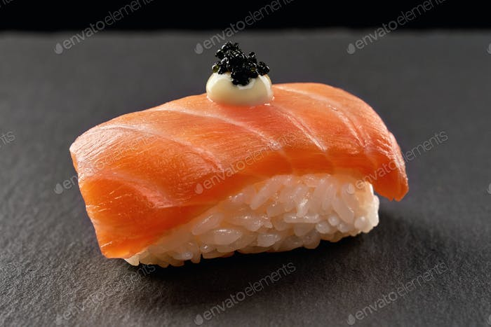 Sake nigiri sushi topped with sauce and black caviar