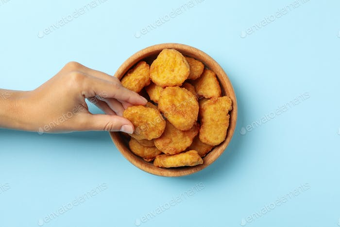 Female hand holds nugget over the blue background with bowl of nuggets