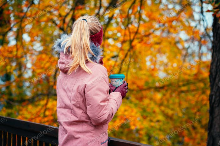 Adult blond woman holds a cup of herbal tee in hands in beautiful autumn forest golden leaves in