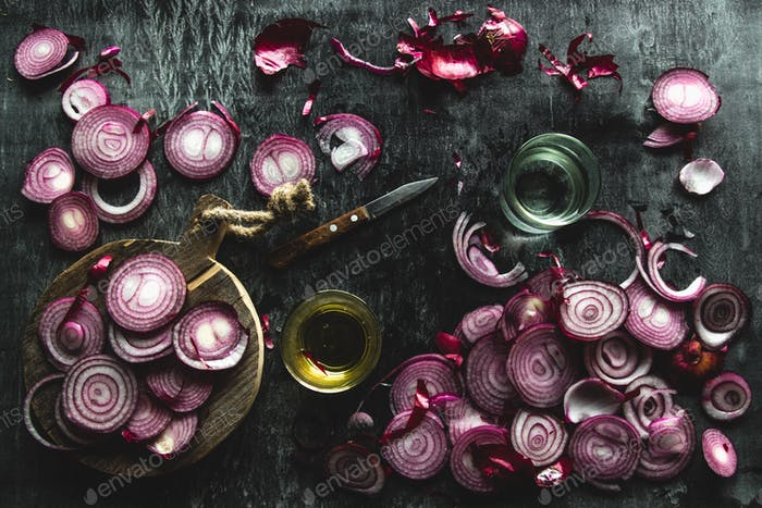 red onions cut into slices on a black background in rustic style. the view from the top. copyspace