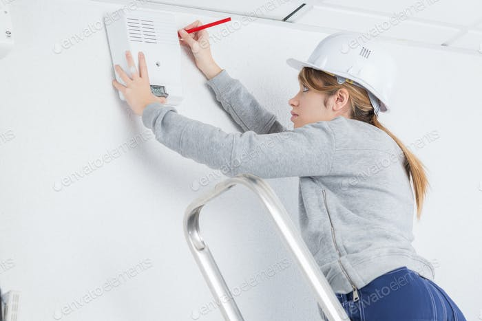 female electrician installing alarm high