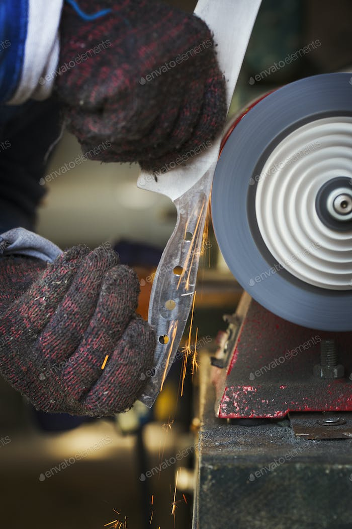 Man in workshop holding a newly cut knife blade, smoothing the surface with a surface grinder.