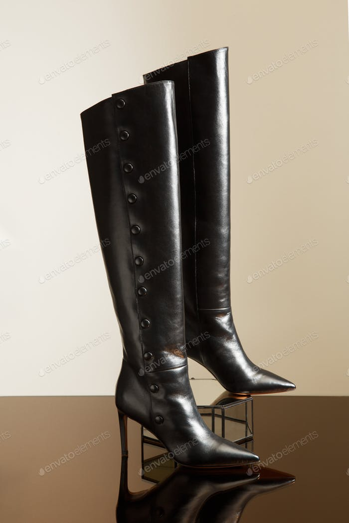 Closeup view of fashionable ladies high heel leather over the knee boots on glass stand.