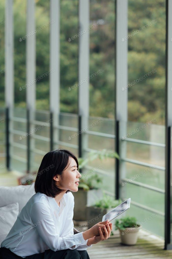 Asian businesswoman using ipad at office window