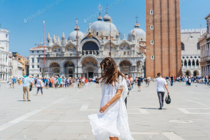young girl is walking around the city square