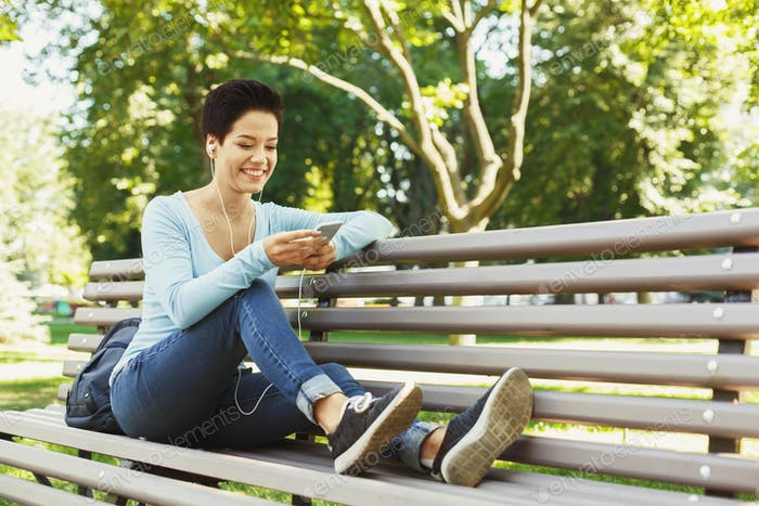Attractive woman listening to music outdoors