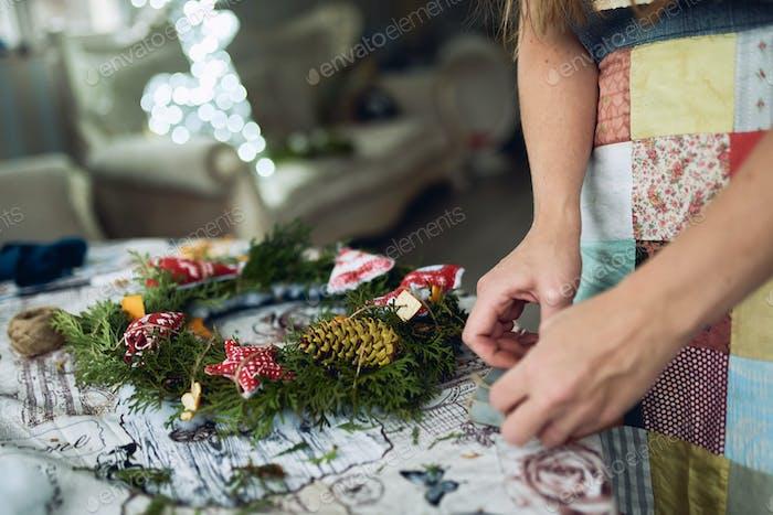 Девушка Флорист декоратор делает рождественский праздничный венок