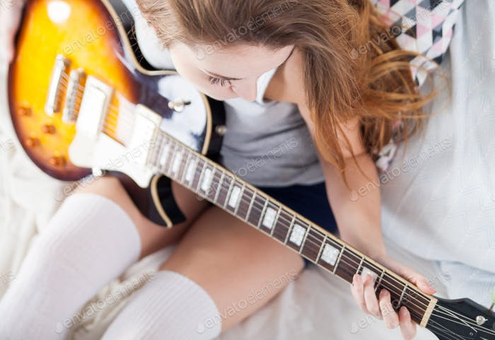 Young girl playing guitar in bedroom at home