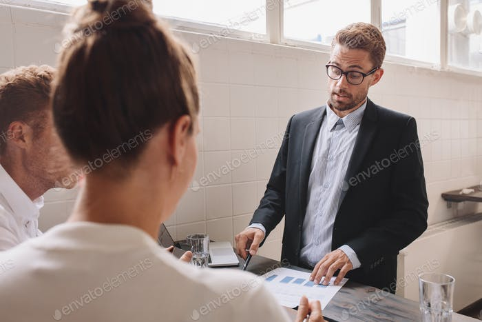 Businessman explaining new business ideas to coworker