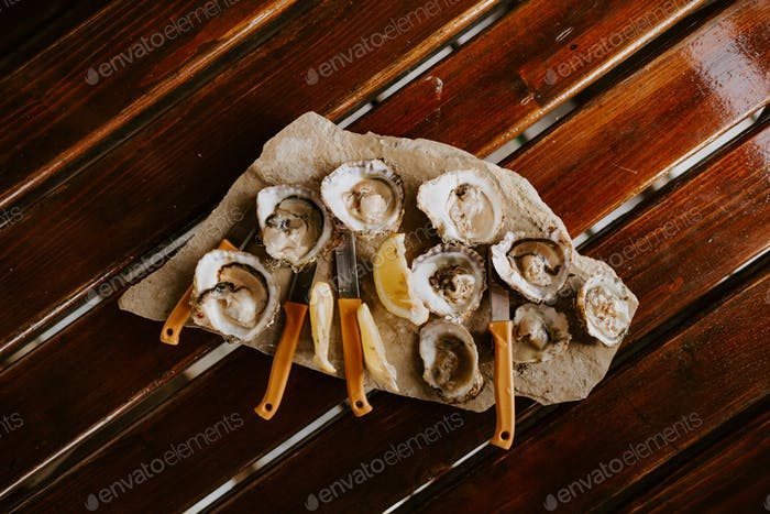 fresh oysters eating with lemon on wooden table