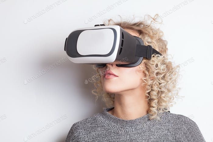 young curly blonde woman in VR glasses
