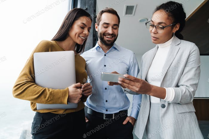 Portrait of colleagues talking and using cellphone while working in office