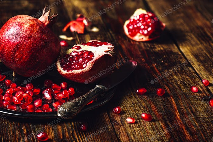 Whole and Opened Pomegranates on Plate
