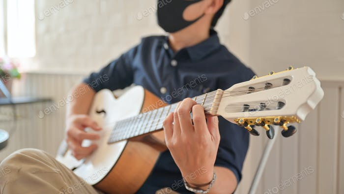 A young man wearing a mask playing guitar at home,Stay at home,Work from home.