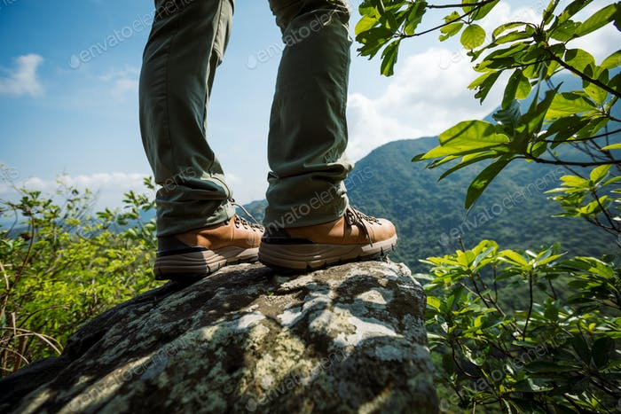 Hiker legs stand on mountain top cliff edge