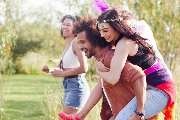 Group Of Friends Walking Back To Tent After Outdoor Music Festival With Men Giving Women Piggybacks