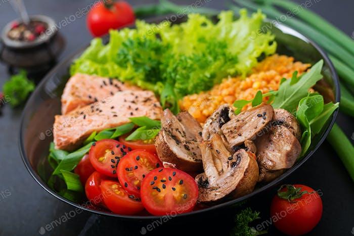 Gesunder Salat mit Lachs, Tomaten, Pilzen, Salat und Linsen auf dunklem Hintergrund