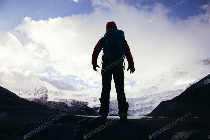 Strong woman backpacker hiking in winter mountains