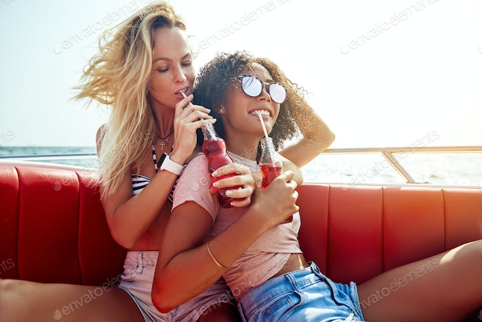 Laughing girlfriends relaxing over drinks on a boat during vacation