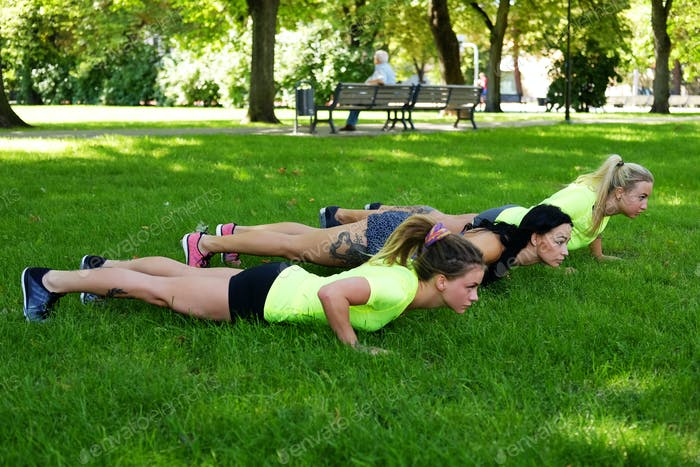 Females warming up on a lawn in summer park.