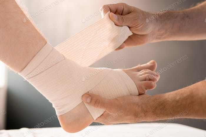 Hands of clinician wrapping foot and leg of patient with flexible bandage