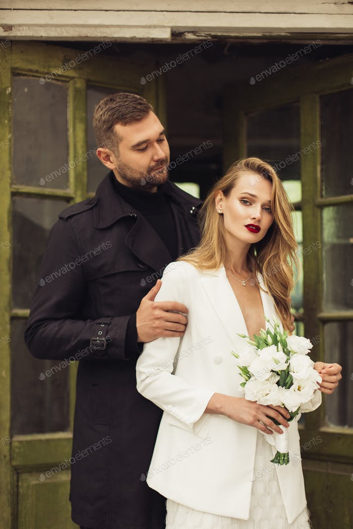Young attractive man in black trench coat and beautiful woman in