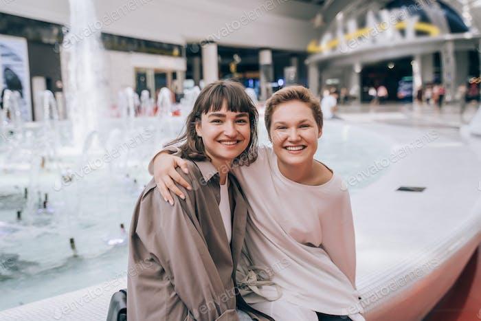Dos chicas se divierten en el centro comercial, una fuente en el fondo