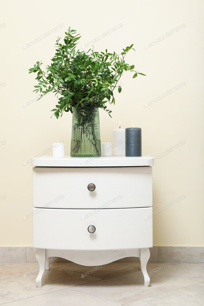 Nightstand with vase with plant and candles