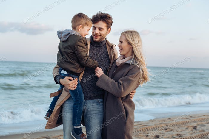 happy family with son standing at seaside in autumn