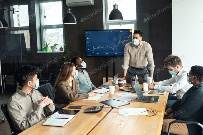 Colleagues in masks having meeting in boardroom, businessman making presentation