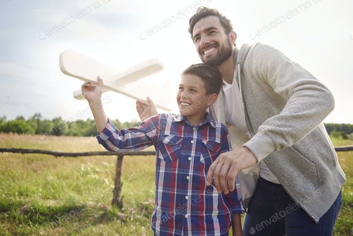 Father and son testing a paper plane