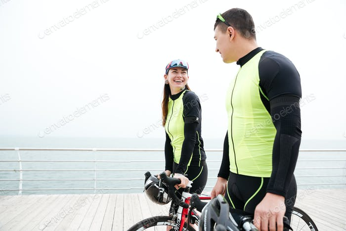 Couple with bicycles walking near the sea and talking