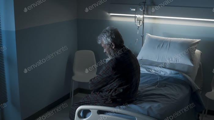 Depressed lonely senior sitting on a hospital bed at night
