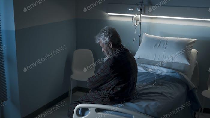 Depressiv einsam Senior sitzt auf einem Krankenhausbett in der Nacht