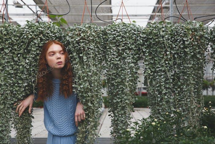 Mädchen versteckt sich hinter grünen Pflanzen