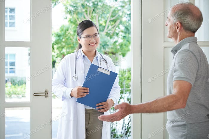 Senior man welcoming doctor at home