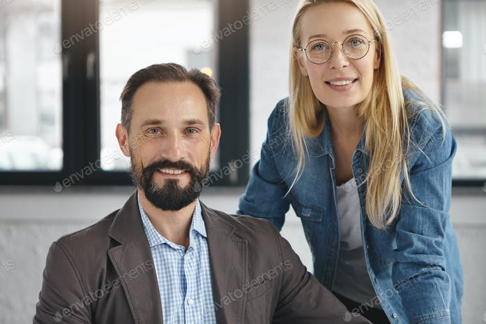Photo of successful business partners or companions, study legal documents, have happy expressions a