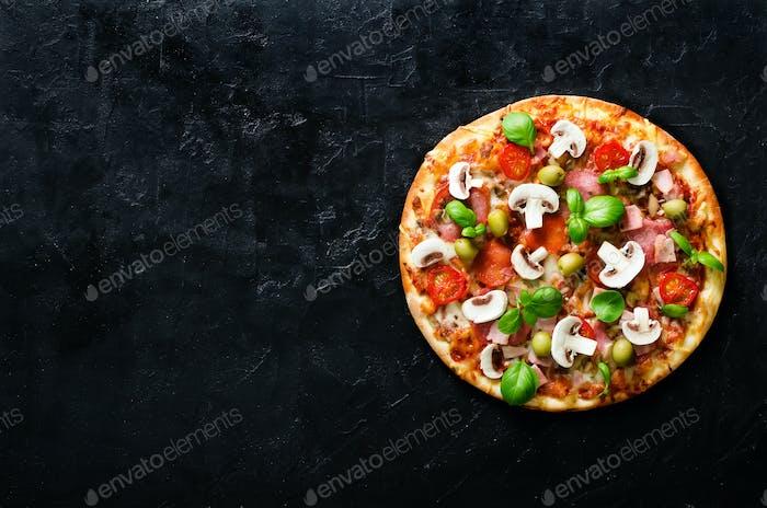 Frische italienische Pizza mit Pilzen, Schinken, Tomaten, Käse, Oliven, Basilikum auf schwarzem Betonuntergrund