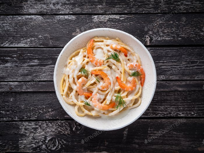 italian pasta spaghetti with shrimps, bechamel sauce and chopped dill