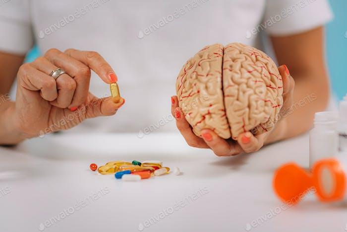 Kognitive Verbesserung oder Gehirnpräparate. Frau hält eine Ergänzung Kapsel und ein Modell Gehirn.