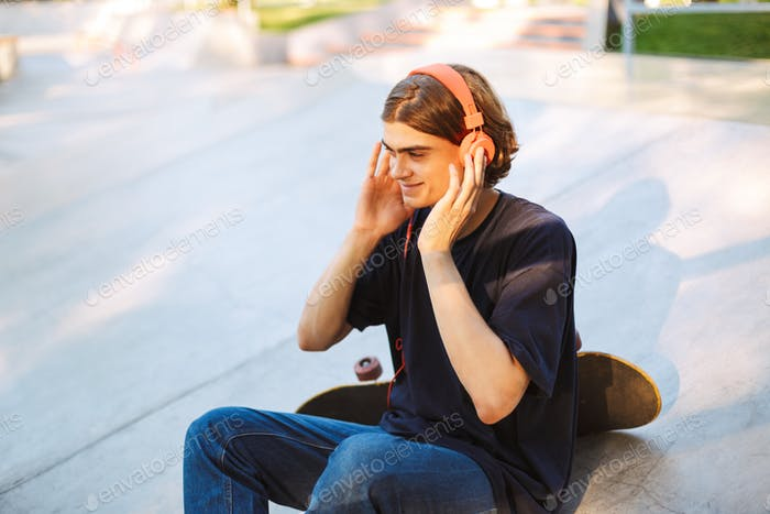 Young smiling guy in orange headphones happily listening music w
