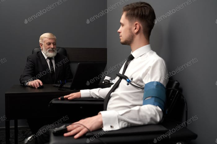Skilled man asking question to patient on lie test